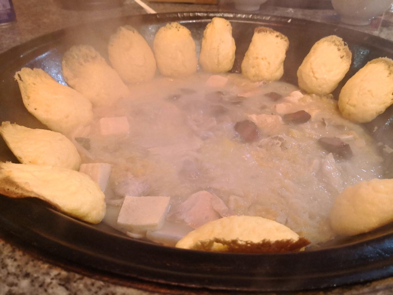 巨大な鉄鍋に貼り付けられたとうもろこし饅頭